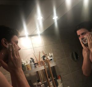 homme entrain de se raser devant un miroir